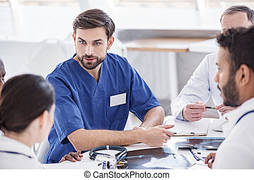 Thrilled doctor arguing with associates during meeting -...