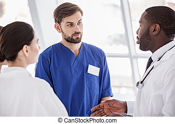 Serene medical advisers arguing in clinic - Calm team of...