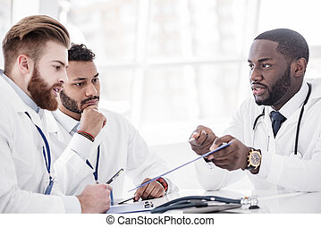 Calm doctors arguing during meeting in office - Serene...