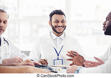 Smiling physician listening his colleagues at meeting -...