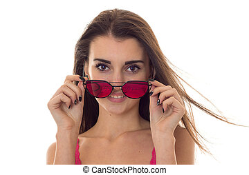 portrait of beauty young girl in pink light shirt looking at the camera and take off sunglasses isolated on white background
