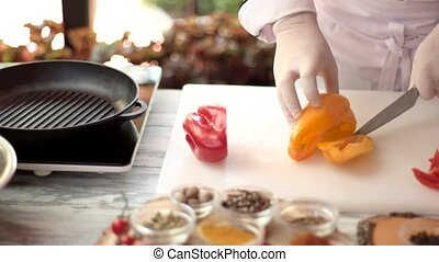 Chef cutting bell pepper. Red and yellow paprika.
