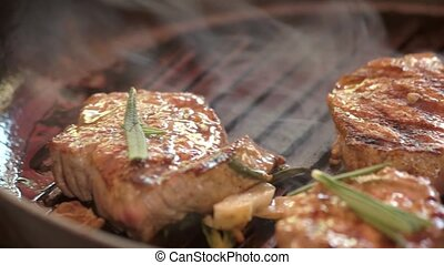 Frying pan with meat pieces. Grilled steaks and rosemary....