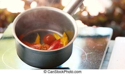 Vegetables in saucepan. Boiled tomatoes and pepper. How to...
