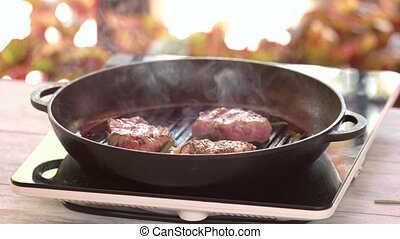 Small steaks in frying pan. Pieces of grilled meat.