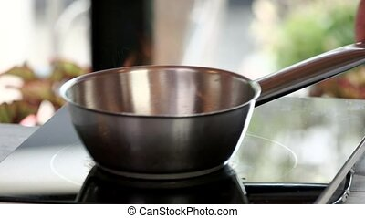 Saucepan on stove. Stainless steel pot.