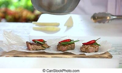 Medallions with chili peppers. Chef adding sauce to food.