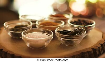 Spices bowls on wooden board. Paprika and cardamom....