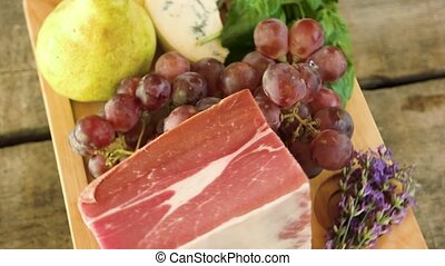 Wooden board with raw food. Frozen meat, cheese and grapes....