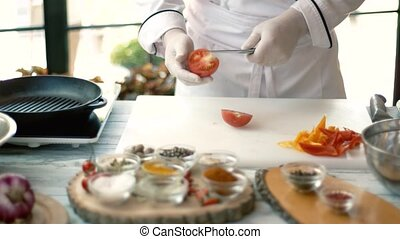 Chef cutting tomato. Cooking board and vegetable pieces....