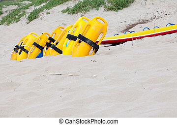 Row of bright yellow floatation devices on beach