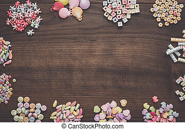 different colorful beads on the brown wooden table with copy...