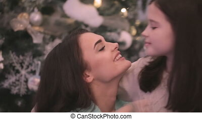 Mother kissing daughter - Happy loving mother kissing and...