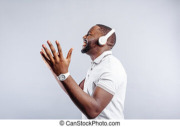 Young man is inspired of great song - Excited african guy is...