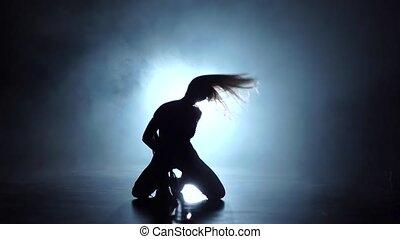 Silhouette pj model grl dancer in smoky studio. Slow motion...