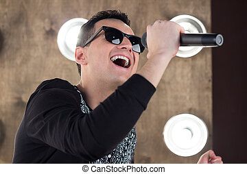 Male singer in sunglasses sings on scene in projectors...