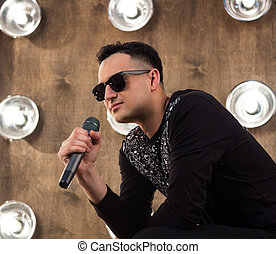 Male pop singer sings on scene in projectors lights - Male...