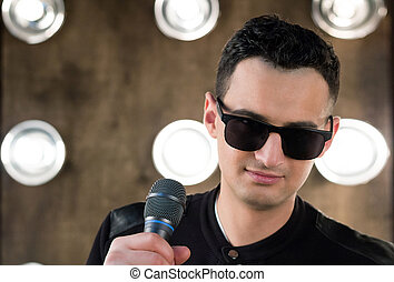 Male singer in sunglasses with microphone performing in...