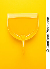 plastic dustpan on yellow background - top view of plastic...