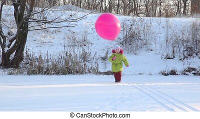 girl plays with air-balloon in snowfield - little girl plays...
