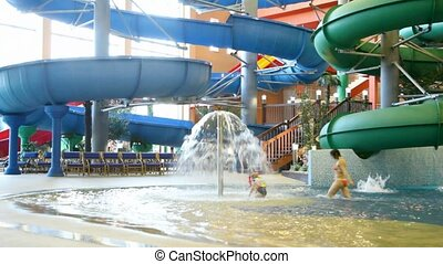 Two children come under fountain in indoor water park - Two...
