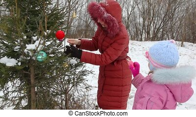 Young mother and daughter decorates the Christmas tree -...