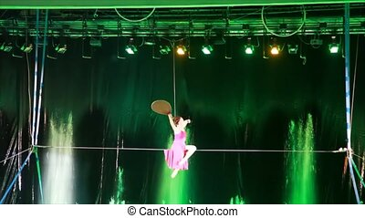 Tightrope walker with fan sits on wire, gets out of it, turns around and goes for it
