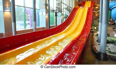 Two boys move out synchronously on slide in large indoor waterpark