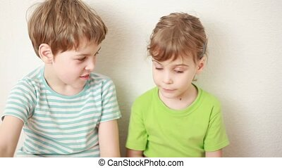 boy and girl sit on floor leaning against wall and boy looks...