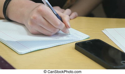 Pupil writes text in exercise book on lesson - Pupil writes...