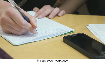 Learner writes text in exercise book on lesson - Learner...