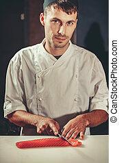 Preparing sashimi set in restaurant kitchen - Young chef...