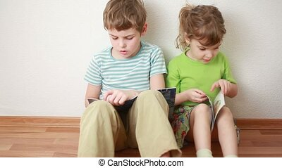 boy and girl sit on floor leaning against wall and read -...