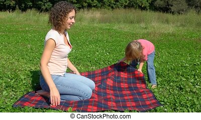 girl looks upside down between legs and young woman in park...