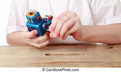 boy turns with winder clockwork robot, and it marches...