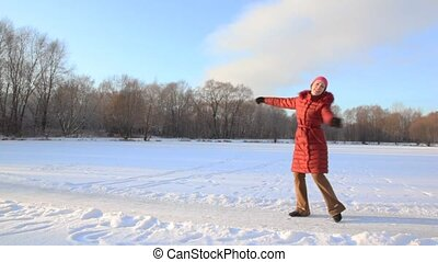 woman spinning in snowfield and throws up snow - happy woman...