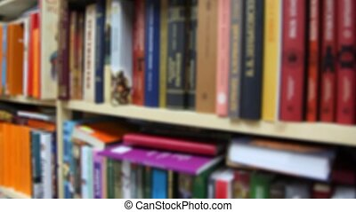 books on bookshelfs in bookshop, vertical panning, defocused