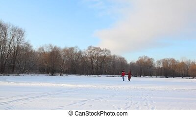 man and woman runs to camera in snowfield - happy man and...