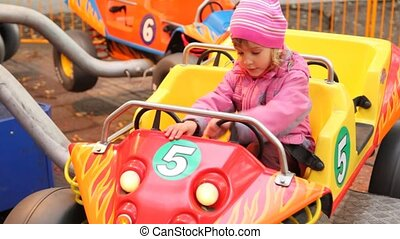 Cute little girl sits in car park amusement - cute smiling...
