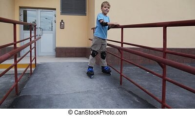 boy in elstringed pads and knee-pads rollerblading near...