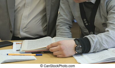 Two learners flip pages of textbook at lesson - Two learners...