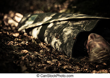 Dead body of a teenage boy lying in a forest - Dead body of...