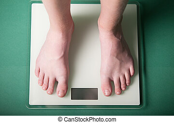 Young boy weighing himself on a scale - Young boy weighing...