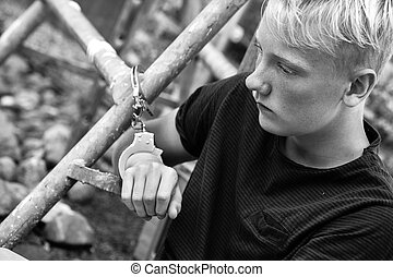 Remorseful young boy handcuffed to a metal bar after his...