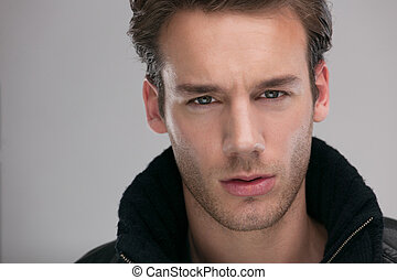 portrait of a young guy over gray background - Fashion man,...