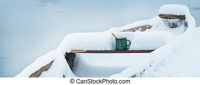 Cold winter and hot tea - Cup with a hot drink. Winter shore...