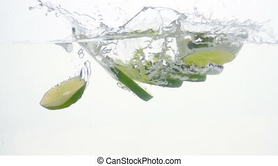 Lime Slices are Falling Through Water.Light Background. Slow...