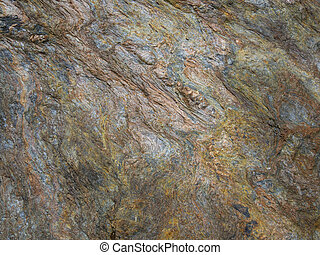 Detail of Metamorphic rocks with colorful mineral streaks.   Texture - background