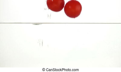 Whole Tomatoes Falling Through Water. Light Background. Slow...