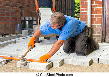 Builder levelling paving stones as he lays them using a...